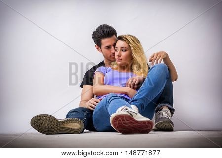 Young couple in love, cuddling, embracing and kissing, studio shot on white background