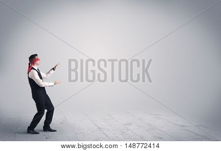 A young male business person in elegant dress standing with red blindfolds in a clear, empty space concept.