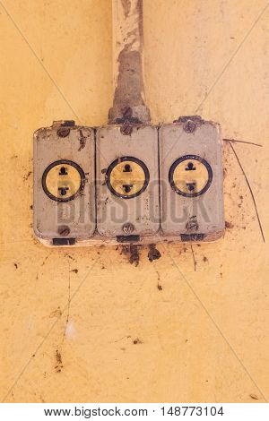 Old and rusty power outlets on yellow wall