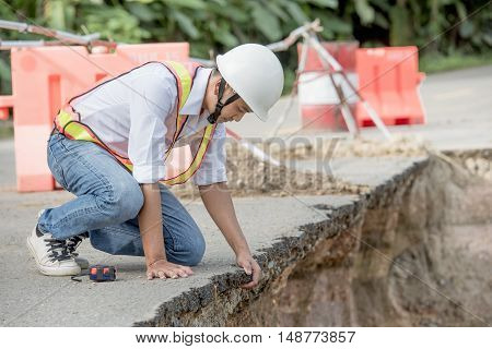 Engineer checking damaged road asphalt concrete design