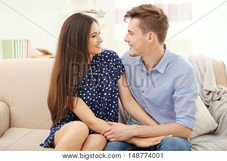 Beautiful young couple sitting on sofa