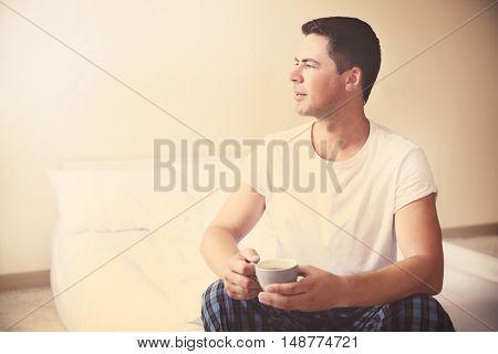 Handsome man tasting morning coffee