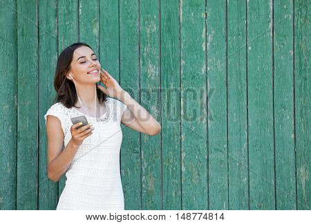 Beautiful girl listening music on wooden background