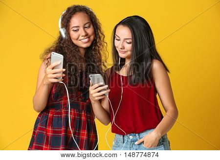 Beautiful girls listening music on yellow background
