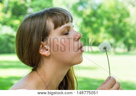 Young Woman Blowing Dandelion Flower