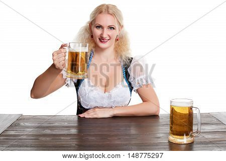 Beautiful young blond girl drinks out of oktoberfest beer stein. Isolated on white background. sits by the table