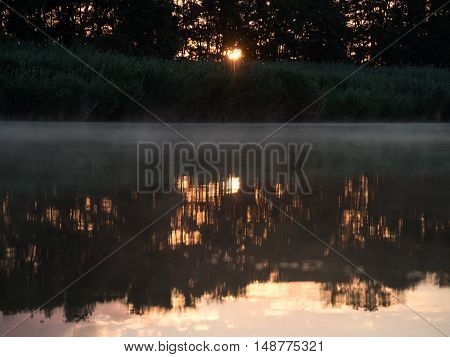 Sunrise in the river with reflex. Mirrored forest line on the river. Fantastic foggy river with fresh green grass in the sunny beams. Dramatic colorful scenery.