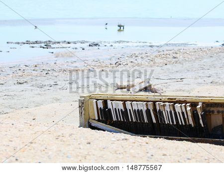 A broken piano carelessly discarded on the shore of the Salton Sea near Bombay Beach in California USA.
