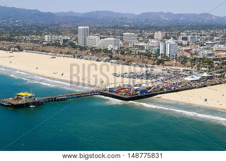 LOS ANGELES, USA - MAY 27, 2015: Aerial view of the Santa Monica Pier with the amusement park Pacific Park also on the picture the beach the ocean and Santa Monica.