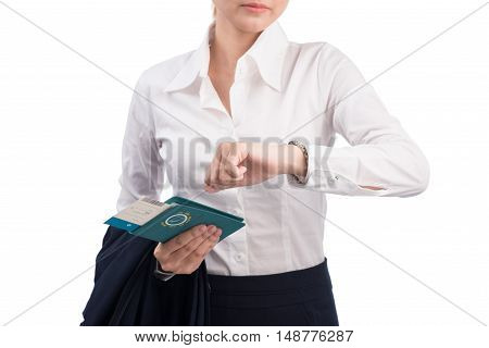 Woman holding passport and ticket looking at watch and worrying about time standing isolated on white background.