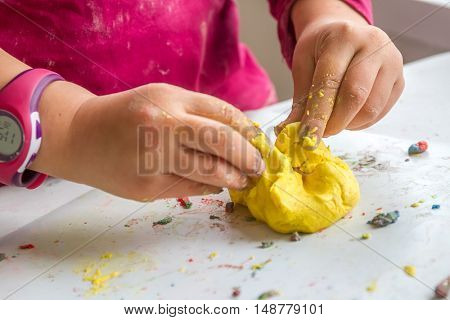 indoor portrait of young happy smiling caucasian child girl playing with play dough