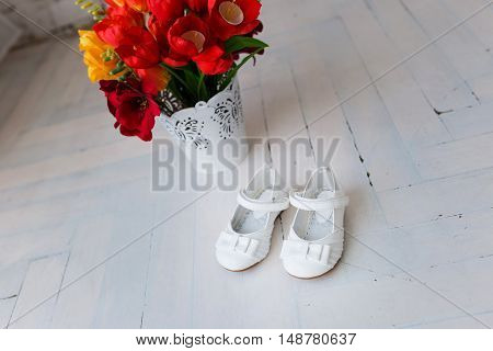 children's white shoes in the background of red flowers