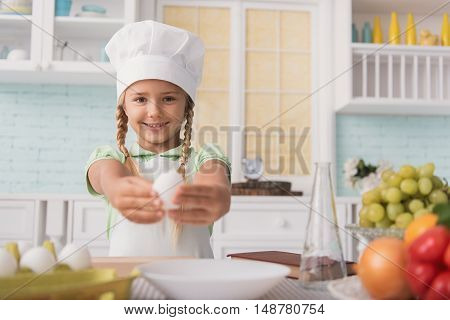 Happy girl is cooking in kitchen. She is holding egg and stretching it to camera. Kid is standing and smiling