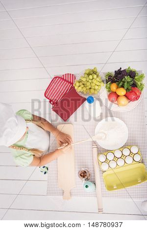 Top view of little girl baking in kitchen. She is holding wooden spoon and taking flour from plate. Kid is standing near table with food
