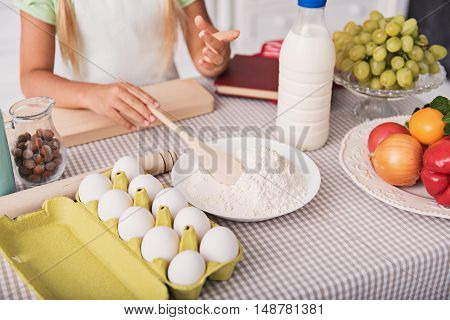 Close up of girl arms holding wooden spoon in plate with flour. She is standing in kitchen. Ready to bake