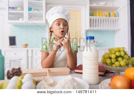 Little girl is cooking in kitchen. She is looking at her finger in flour with shock
