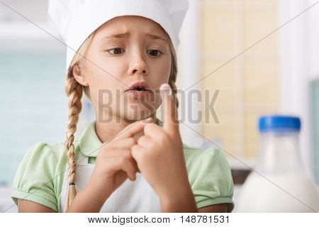 Shocked child became dirty with flour. She is looking at her finger with fear. Girl is standing in kitchen and wearing chef hat