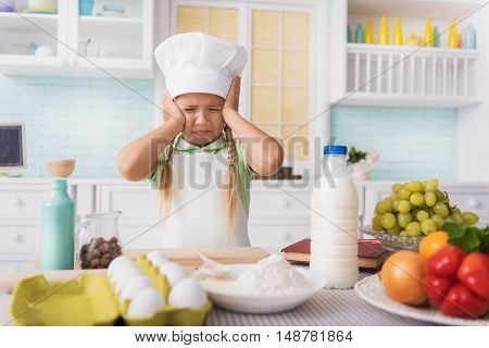 Little girl is afraid of cooking. She closed her eyes with disappointment and crying. Child is standing in kitchen and touching her head