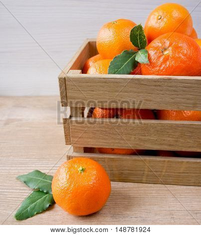 Wooden box with tangerines on a wooden table