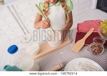 Inspired little girl is mixing batter in kitchen. She is standing near table and smiling