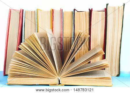 Open book stack of colorful hardback books isolated on white background. Back to school. Copy space for text. Toned image.