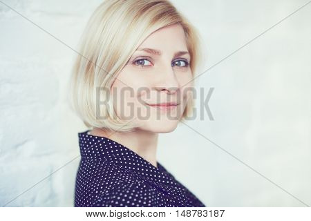 Closeup photo of young blonde woman looking at camera.