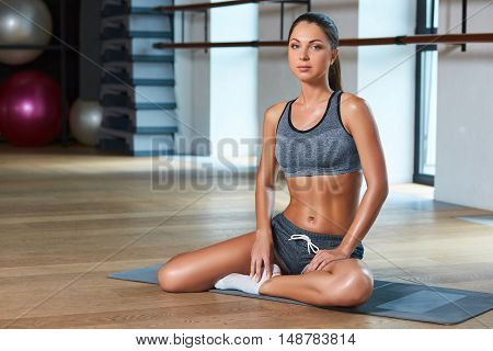 Gorgeous suntanned brunette doing exercises a the gym. girl sitting on the mat, preparing for sports