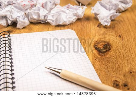 Blank graph notebook and crumpled drafts - Math spiral notebook with a pen on it and thrown crumpled pages in the background on a wooden desk.