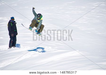 Snowdorder trick in air jump with shadow on ground on ski resort in winter season. Extreme sport concept. Copy space for advertising.