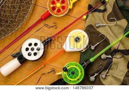 Fishing accessories consisting of tackles weights hook net. Wooden background. Outdoor activity and leisure concept.