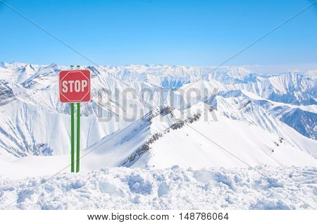 Sign stop on ski resort high in mountains. Place for freeride with powder. Dangerous snowy way or trail. Big beautiful peaks and clean blue sky background.