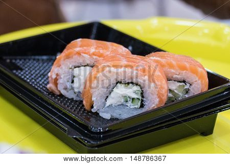 Sushi rolls philadelphia in black plastic plate on yellow table