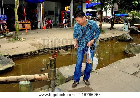 Ping Le China - September 28 2010: Tourist tries out an old cast-iron water pump with a bamboo draining pipe