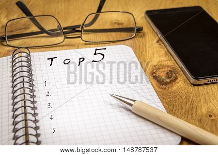 Top five list concept - Ranking concept for a top 5 preferences list written on a graph spiral notebook sheet placed on a wooden table with eyeglasses and a phone in the background.