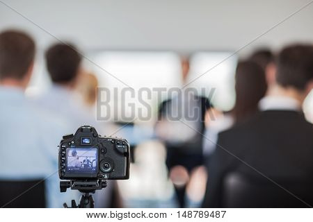 Camera on tripod at press conference of business people
