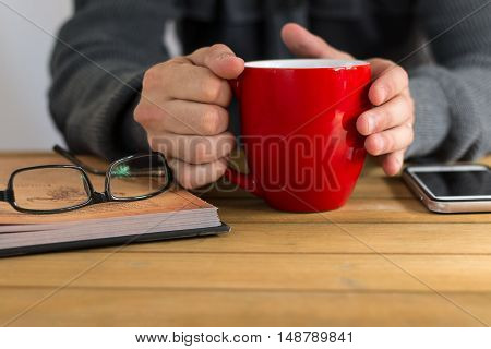 Close up shot of hands holding a coffee mug, with book, glasses and a cellphone next to it