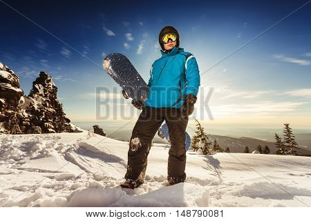 Bright color snowboarder posing on blue sky backdrop. Sheregesh, Siberia, Russia