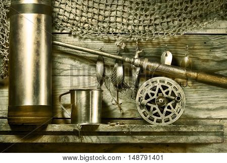Set for fishing on the shelf. Toned sepia. On a wooden background