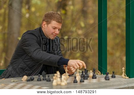 Young man in autumn park puts figure on chess table in gazebo