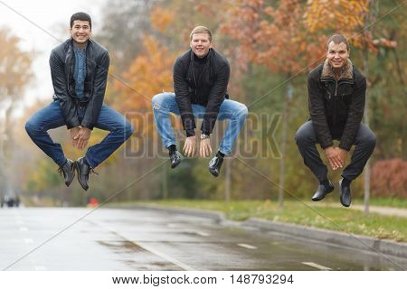 Three young men in black jackets jumping for joke in alley in park