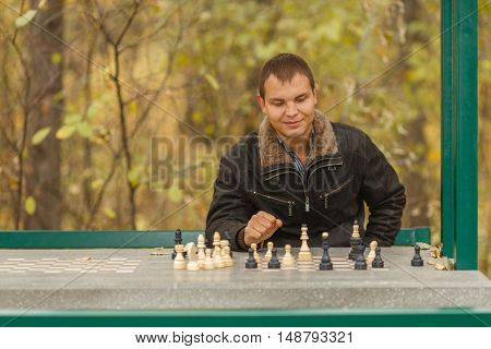portrait of young man in black jacket in gazebo playing chess