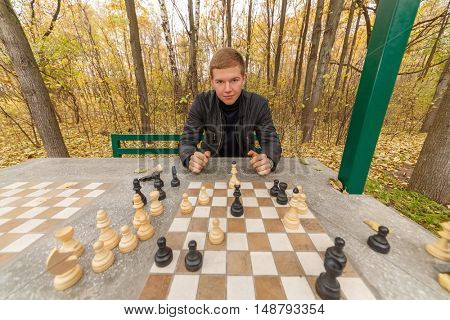 portrait of young man in black at chess table in autumn park