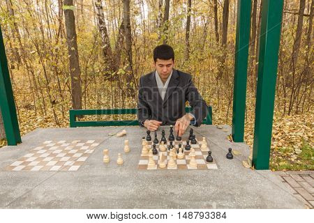 young man in gray coat in park puts figure on chess table in gazebo