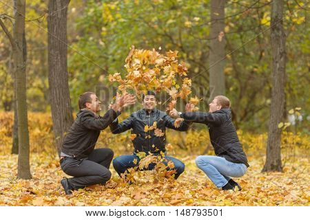 Three men in black jackets hunker down and pop-up yellow maple leaves in park