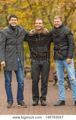 three friends dressed in warm clothes standing in alley in park, embracing and laughing