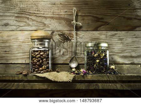 Coffee beans and dry tea in glass jars on the shelf. On a wooden background