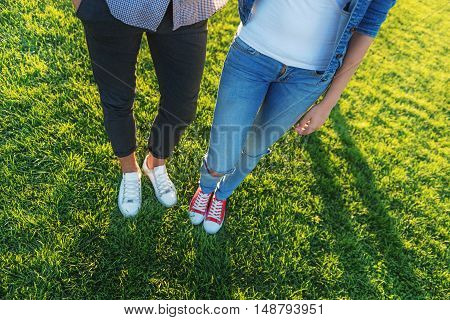 waist down view of couple on the green grass with copy space