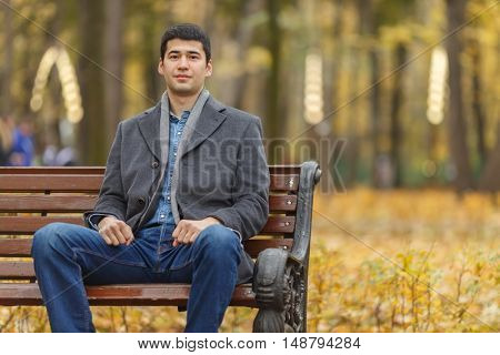 portrait of young man in gray coat and jeans sitting on bench in alley in autumn park