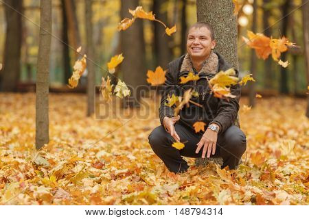 young man in black jacket in autumn park, crouched near tree, throws up yellow autumn leaves, smiling