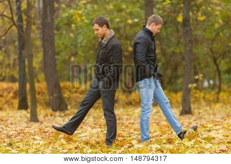 Full portrait of two friends walking in autumn park, under feet of yellow foliage